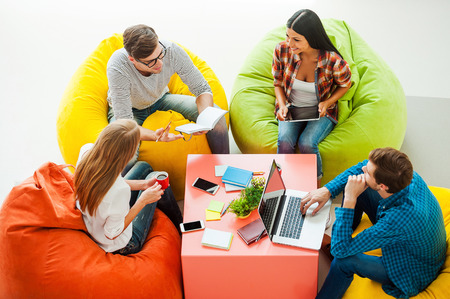 idea: Place where ideas born. Top view of four young people working together while sitting at the colorful bean bags
