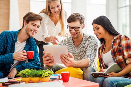 Trabajando en proyecto creativo juntos. Grupo de gente joven feliz que mira la tablilla digital mientras que se sienta en las bolsas de colores de frijol en la oficina Foto de archivo - 43053440
