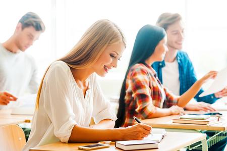 persona escribiendo: Estudiar con placer. Mujer joven feliz escribiendo en el bloc de notas y sonriendo mientras est� sentado en su escritorio en el aula Foto de archivo