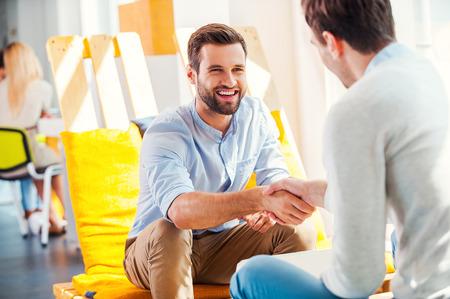 stretta di mano: Siglando un accordo! Due giovani uomini felici agitando le mani mentre era seduto nella zona resto dell'ufficio