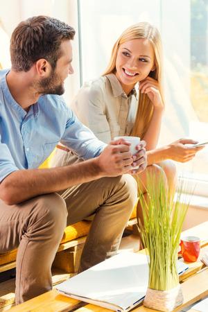 empleado de oficina: descanso para tomar café con su colega. mujer joven que sostiene el teléfono móvil mientras que el hombre joven que sostiene la taza de café y sentarse cerca de ella en el área de descanso de la oficina sonriendo
