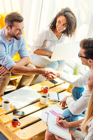 man in office: Welcome on board! Two cheerful young men sitting at the wooden desk in office and shaking hands while two beautiful women looking at them and smiling Stock Photo