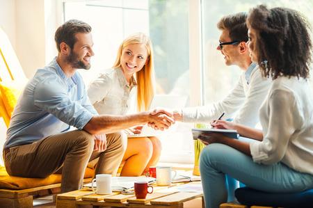 personas saludandose: Bienvenido a nuestro equipo! Dos felices womenworking joven togetherat el �rea de descanso, mientras que dos hombres d�ndose la mano y sonriendo Foto de archivo