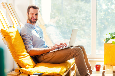 looking at view: Working with pleasure. Side view of smiling young man working on laptop and looking at camera while sitting in the rest area of the office