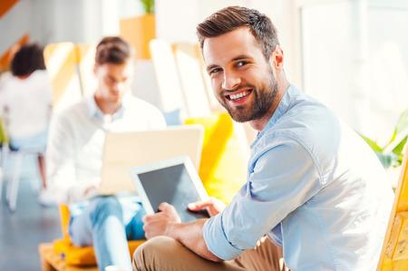 personas sentadas: Hombre de negocios joven confidente. Hombre joven feliz que sostiene la tablilla digital y mirando a la c�mara mientras que sus colegas que trabajan en segundo plano