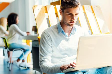 Hij is altijd hard aan het werk. Geconcentreerde jonge man werken op de laptop, terwijl zijn collega's die werken op de achtergrond Stockfoto