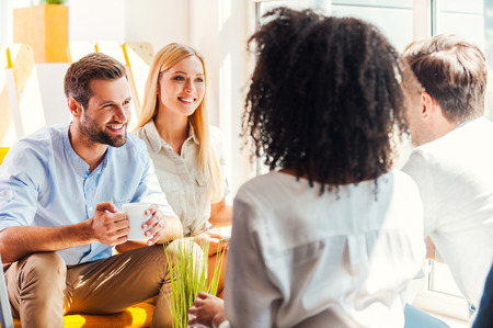 professional man: Sharing some office news. Group of happy young people discussing something while sitting in the rest area of the office Stock Photo