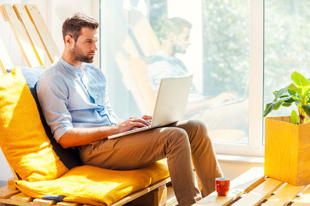 empleado de oficina: Concentrado en su trabajo. Vista lateral del hombre joven concentrado trabaja en la computadora port�til mientras est� sentado en el �rea de descanso de la oficina Foto de archivo