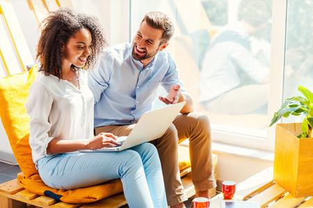 gente trabajando: Compartiendo sus ideas. Mujer africana joven que trabaja en la computadora portátil mientras que el hombre sentado cerca de ella en el área de descanso de la oficina Sonriente