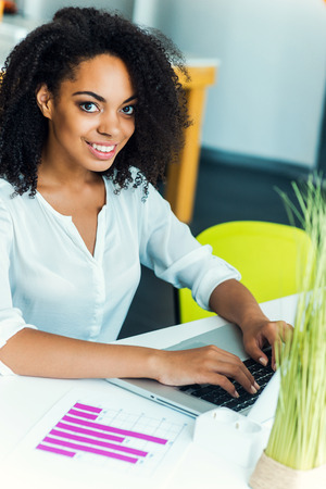 business woman working: Staying positive at work. Smiling young African women working on laptop and looking at camera while sitting at working place Stock Photo