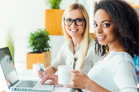 Twee hoofden zijn beter dan één. Twee glimlachende jonge vrouwen kijken naar de camera en lacht tijdens de vergadering op de werkplek Stockfoto - 43053536