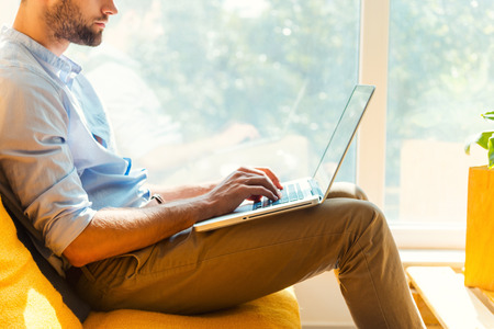 personas sentadas: Centrado en su trabajo. Primer plano de hombre joven que trabaja en la computadora port�til mientras est� sentado en el �rea de descanso de la oficina Foto de archivo