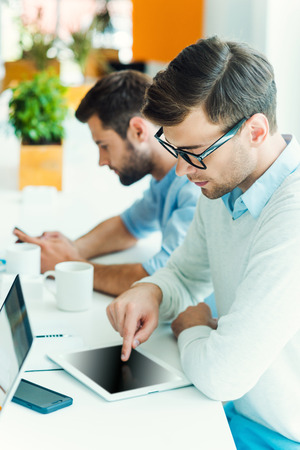 business idea: Concentrated on work. Concentrated young man working on digital tablet while his colleague holding mobile phone in the background