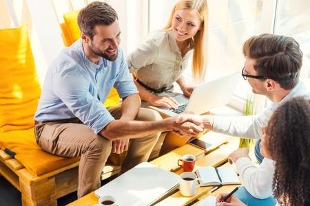 Herzliche Glückwünsche! Zwei freundliche junge Männer sitzen auf dem hölzernen Schreibtisch im Büro und Hände schütteln, während zwei schöne Frauen Blick auf sie und lächelt Standard-Bild - 43008677