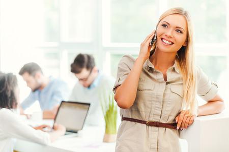 mujer alegre: Mantener el contacto con los clientes. mujer joven alegre que habla en el teléfono móvil y sonriendo mientras sus colegas que trabajan en segundo plano