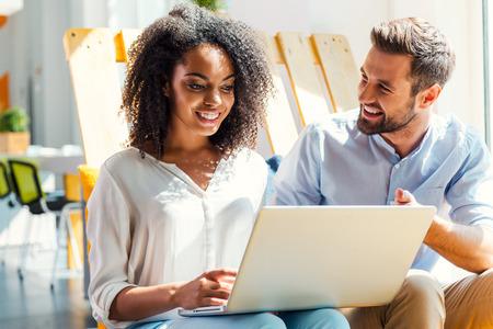 Zakelijke bespreking. Glimlachend jonge Afrikaanse vrouw werken op de laptop, terwijl man zit in de buurt van haar en gebaren