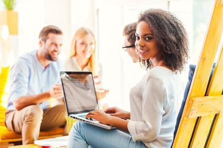 창의적인 환경에서 일하기. 배경에서 뭔가 논의하는 그녀의 동료 동안 노트북에서 작동하는 젊은 아프리카 여자 웃는