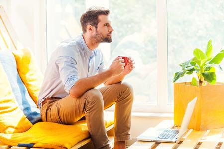 hombre pensando: El subir con nuevas ideas. Vista lateral de la joven serio que sostiene la taza de café y mirando a otro lado mientras se está sentado en el área de descanso de la oficina