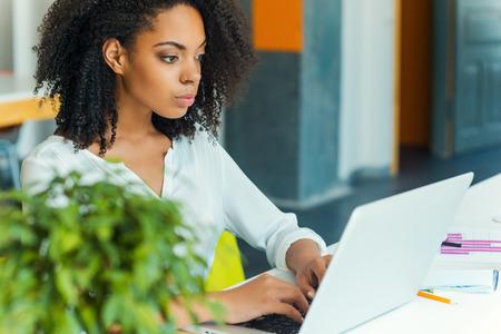 노력은 성공을 보장합니다. 작업 장소에 앉아있는 동안 노트북에서 작동 집중 젊은 아프리카 여성