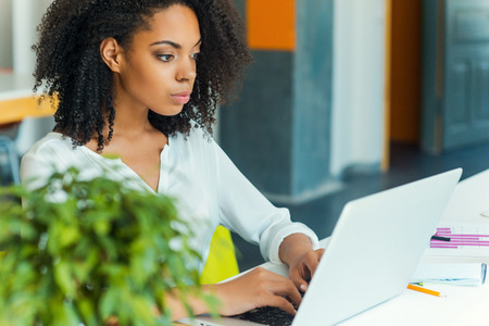 femme africaine: Le travail dur assure le succès. Concentrés jeunes femmes africaines travaillant sur un ordinateur portable alors qu'il était assis au lieu de travail Banque d'images