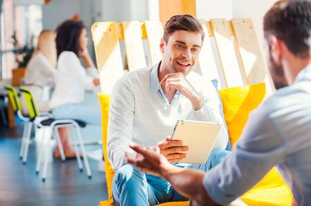 협업은 성공의 열쇠입니다. 웃는 젊은 남자 디지털 태블릿을 들고 사람이 사무실의 나머지 지역에서 그를 맞은 편에 앉아 뭔가를 논의 스톡 콘텐츠