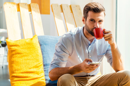 tomando café: Inspirado con una taza de café recién hecho. Hombre joven hermoso que sostiene el teléfono móvil y el consumo de café mientras estaba sentado en el área de descanso de la oficina