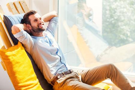 hombres guapos: Relajaci�n total. Alegre joven sosteniendo la cabeza en la mano y sonriendo mientras estaba sentado en el �rea de descanso de la oficina