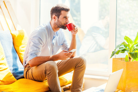 work area: Fresh coffee for fresh ideas. Handsome young man holding mobile phone and drinking coffee while sitting in the rest area of the office