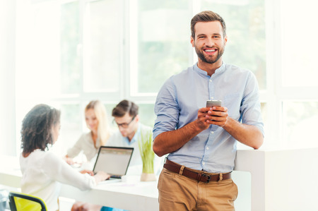 Genieten van het leven op kantoor. Blije jonge man met mobiele telefoon en kijken naar de camera terwijl zijn collega's die werken op de achtergrond Stockfoto