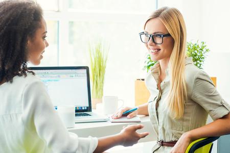 Discuter de travailler ensemble. Deux jeunes femmes heureuses discuter de quelque chose alors qu'il était assis sur leur lieu de travail ensemble Banque d'images - 43008748