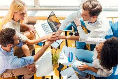 Buen equipo de trabajo! Vista superior de cuatro jóvenes feliz celebración de las manos unidas mientras se está sentado en el escritorio de madera juntos Foto de archivo - 43008750