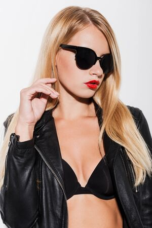 sex pose: Beauty in style. Beautiful young woman in black bra and leather jacket looking away while standing against white background