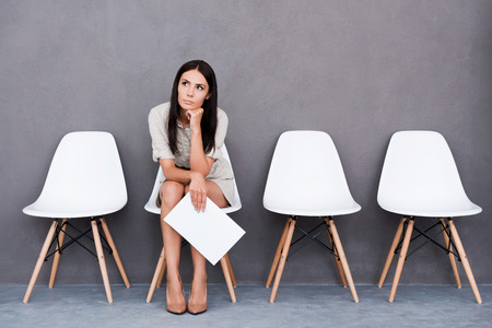 mujer pensativa: Aburrido joven empresaria celebraci�n de papel y mirando a otro lado mientras se est� sentado en la silla contra el fondo gris