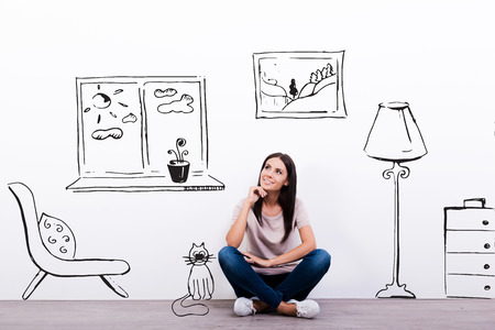 Dreaming about new house. Thoughtful young woman looking at the sketch on the wall while sitting on the floor Фото со стока