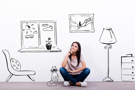 Sueño sobre nueva casa. Mujer joven pensativa mirando el dibujo en la pared mientras se está sentado en el suelo