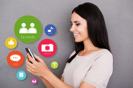 smart phone woman: Cheerful young woman holding smart phone with colorful icons around it Stock Photo