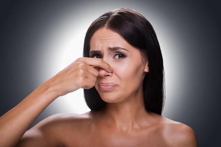making a face: Portrait of frustrated young shirtless woman holding fingers on nose and making a face while standing against grey background Stock Photo