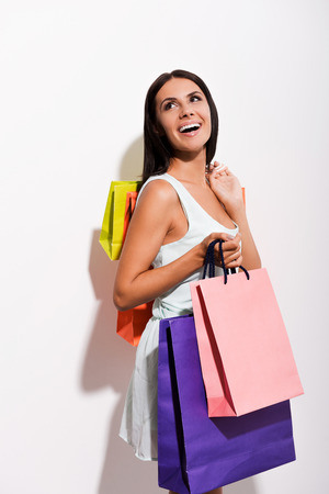 shoulder carrying: Excited young woman in dress carrying colorful shopping bags and looking over shoulder with smile while standing against white background