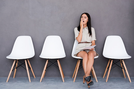 Bored young businesswoman holding paper and looking away while sitting on chair against grey background Zdjęcie Seryjne