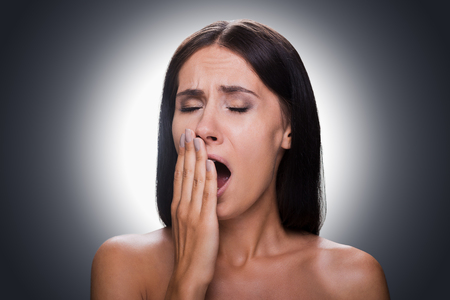 tired eyes: Portrait of bored young shirtless woman covering mouth by hand and yawning while standing against grey background