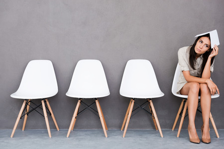 entrevista de trabajo: Aburrido joven empresaria celebración de papel en la cabeza y mirando a otro lado mientras se está sentado en la silla contra el fondo gris Foto de archivo