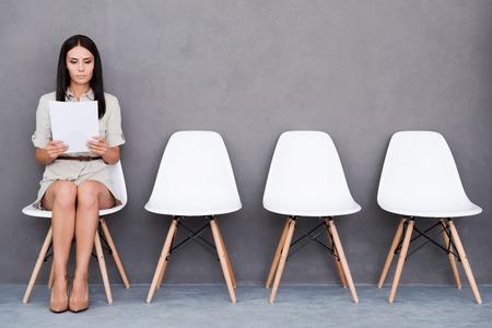 Berzeugte junge Geschäftsfrau, die Papier, während sitzt auf dem Stuhl vor grauem Hintergrund Standard-Bild - 43296991