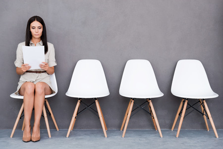 Confident young businesswoman holding paper while sitting on chair against grey background Archivio Fotografico