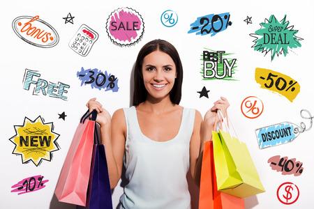 カラフルなショッピング バッグを運ぶと、彼女の頭の上にカラフルなスケッチでカメラを見てドレスを着て陽気な若い女性 写真素材
