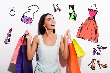Excited young woman in dress carrying colorful shopping bags and looking up with colorful sketches upon her head