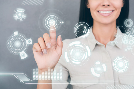 human finger: Cropped image of young woman touching transparent screen and smiling Stock Photo