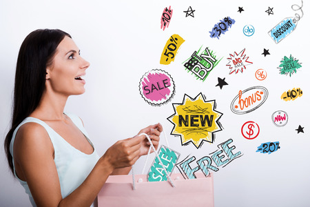 woman side view: Side view of surprised young woman in dress carrying shopping bag and looking at the colorful sketches Stock Photo