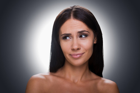 irritating: Portrait of frustrated young shirtless woman looking away and grimacing while standing against grey background Stock Photo
