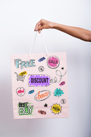 unrecognizable person: Close-up of female hand holding shopping bag with colorful sketches on it