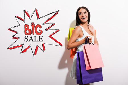 boca abierta: Feliz mujer joven en traje de llevar bolsas de la compra de colores y mirando por encima del hombro en el dibujo colorido